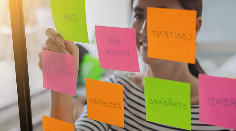 Woman writing on post it - UX Research - All you need to know about UX Design